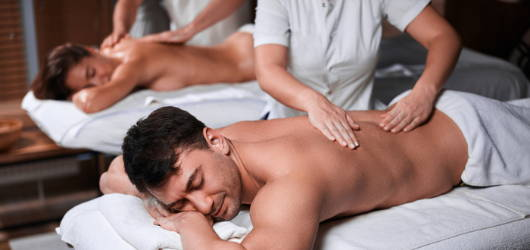 couple relaxing in a side by side couples massage