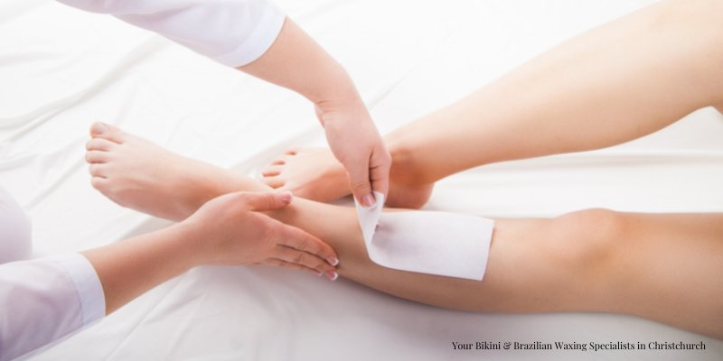 Beauty therapist performing body waxing
